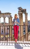 Tourist woman near Roman Forum in Rome, Italy having excursion. Roman Holiday. Full length portrait of smiling stylish tourist woman near Roman Forum in Rome Stock Images