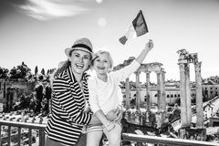 Mother and child tourists in front of Roman Forum rising flag. Roman Holiday. smiling modern mother and child tourists in the front of Roman Forum in Rome, Italy Royalty Free Stock Images