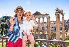 Smiling mother and child tourists near Roman Forum handwaving Stock Photos