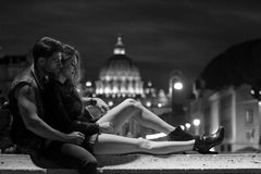 Roman holiday. Young couple at night on St. Angelo bridge with view of St. Peter's Basilica on a background, Rome Stock Image