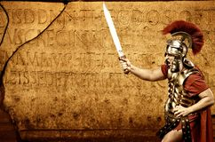 Roman legionary soldier. In front of abstract wall Royalty Free Stock Photos
