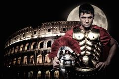 Roman legionary soldier. In front of coliseum at night time Stock Photos