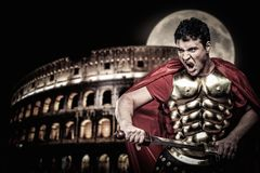Roman legionary soldier. In front of coliseum at night time Stock Photo