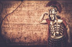 Roman legionary soldier. In front of  wall with ancient writing Royalty Free Stock Photography
