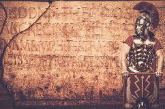 Roman legionary soldier. In front of  wall with ancient writing Stock Images