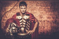 Roman legionary soldier. In front of  wall with ancient writing Stock Photo