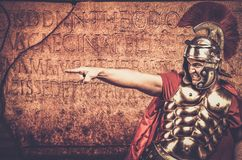 Roman legionary soldier. In front of  wall with ancient writing Royalty Free Stock Photos