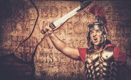 Roman legionary soldier. In front of  wall with ancient writing Stock Photography