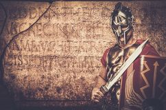 Roman legionary soldier. In front of  wall with ancient writing Stock Photos