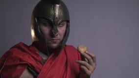 Roman Legionnaire i röd tunika äter kakor arkivfilmer