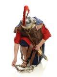 Roman militair die een kroon van doornen opneemt stock fotografie