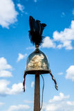 Roman military helmet with black feathers. On top hangs on a wooden pole against the background of blue sky and white clouds Royalty Free Stock Images