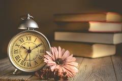 Roman Numeral en despertador del vintage y la pila de fondo del libro Imagen de archivo