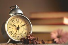 Roman Numeral in Uitstekende Wekker en Stapel van Boekachtergrond Stock Fotografie