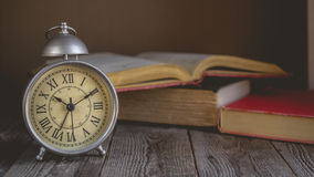 Roman Numeral in Vintage Alarm Clock and Open Book Background wi stock photography