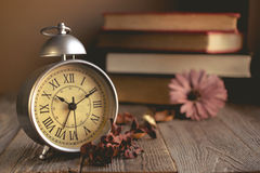 Roman Numeral in Vintage Alarm Clock and Stack of Book Background. With Copy Space for Advertise or Web Promote about the Time or Nostalgia Concept stock images