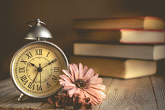Roman Numeral in Vintage Alarm Clock and Stack of Book Background. With Copy Space for Advertise or Web Promote about the Time or Nostalgia Concept stock image