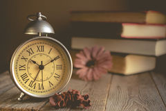 Roman Numeral in Vintage Alarm Clock and Stack of Book Background. With Copy Space for Advertise or Web Promote about the Time or Nostalgia Concept royalty free stock photos