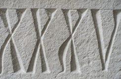Roman Numerals Carved medieval na pedra foto de stock