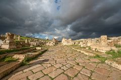 A Roman road in the ancient city of Gerasa after a storm. With dark grey clouds Royalty Free Stock Photography