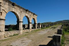 Roman Ruins buildings and long road in volubilis in morocco. View of the Basilica, Volubilis, Morocco. The impressive ruins of this regional Roman capital sit royalty free stock photo