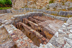 Roman ruins of Conimbriga. Hypocaust structure used to heat the water of the Caldarium room in the Roman Baths of the Wall. Royalty Free Stock Photos