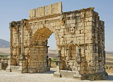 Roman Ruins. The Triumphal Arch at Volubilis in Morocco. The impressive ruins of this regional Roman capital sit surrounded by a mix of desert and fields Royalty Free Stock Images
