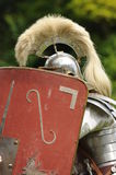 Roman soldier behind shield. Closeup of Roman soldier hiding behind scutum shield outdoors Stock Image