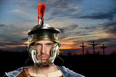 Roman Soldier With Crosses in Background. Portrait of Roman soldier with crossed in background at sunset stock photo