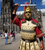 Roman Soldier. A man dressed like a Roman soldier is posing in front of Cologne Cathedral. Cologne Cathedral (High Cathedral of St. Peter) is a Roman Catholic stock photo