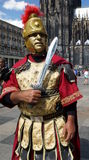 Roman Soldier. A man dressed like a Roman soldier is posing in front of the Cologne Cathedral. Cologne Cathedral (High Cathedral of St. Peter) is a Roman stock photography