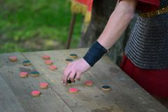 Roman soldier playing a game. Roman soldier playing a board game named merellus or the mill stock photos