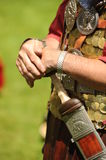 Roman soldier with sword. Details of person wearing historical Roman soldier costume with hands on sword Royalty Free Stock Photo