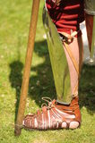 Roman soldier wearing sandal. Details of Roman soldier wearing traditional caliga sandal and holding wooden staff Stock Photography