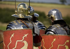 Roman soldiers in armor. Roman soldiers wearing metal armor and holding shields Stock Photos