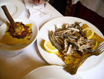 Roman specialties. Examples of seasonal Roman cuisine in springtime: fried artichokes and fresh anchovies with lemon Stock Images