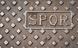 Roman SPQR drain cover. A manhole drain cover in Rome, Italy, with the letters SPQR Royalty Free Stock Images