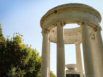 Roman style columns. Roman style ruins, stone columns, in an outdoor setting with a bright blue sky above Royalty Free Stock Image