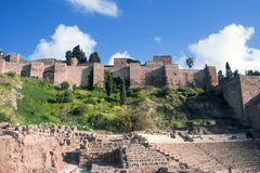 Roman theater on the background of the Alcazaba. People relax on stone benches for spectators on a warm sunny day. stock photography