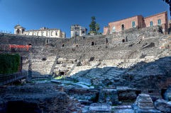 Roman theater, Catania, Sicily, Italy. The stage and seats of the antique Roman theatre in Catania, Sicily, Italy, with houses on the background under a blue sky Royalty Free Stock Image