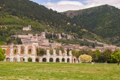 Roman theater of the first century BC and Gubbio town. Ancient Roman theater with panorama on the Gubbio city and hills Stock Photo