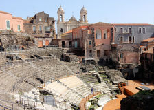 Roman theatre and church - Catania – Sicily. Roman theatre with rows of seats, steps and orchestra – on the background houses and Church of St. Francis of Stock Photography