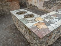 Roman thermopolium in Pompeii, Italy. World Heritage List. Distinctive masonry counter in the interior of ruined Roman shop in the ancient city of Pompeii, near royalty free stock photo