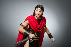 Roman warrior with sword against background Stock Photo
