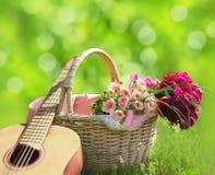 Romance, влюбленность, концепция дня ` s валентинки - плетеная корзина с букетом цветков, гитарой на траве Стоковые Изображения RF