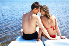 Romance. Back view of two people sitting on deck chairs and looking at one another on resort royalty free stock image