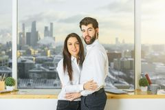 Romance concept. Side view of hugging couple in modern office interior with blurry city view. Romance concept Royalty Free Stock Photography