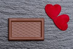 Two red fluffy hearts and a chocolate confection served on the rough black slate background. Romance concept: Two red fluffy hearts and a chocolate confection Stock Image