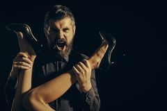 Romance and couple in love. Love and relations, dominating. Legs of woman in shoes at man with beard. Man in shirt isolated on black background. Guy at table stock images