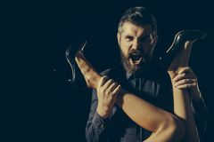 Romance and couple in love. Love and relations, dominating. Legs of woman in shoes at man with beard. Man in shirt isolated on black background. Guy at table stock photography